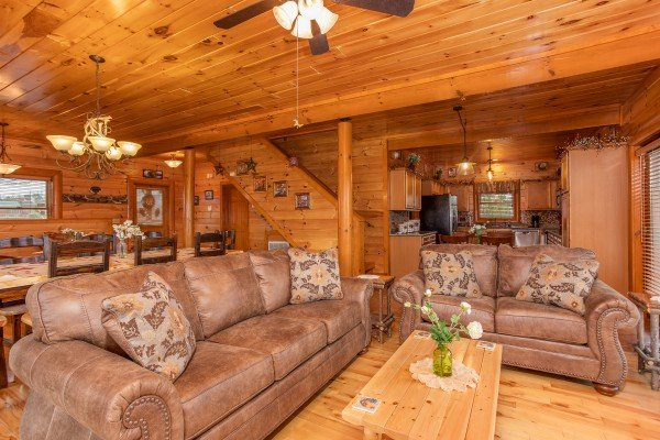 Couch and love seat around a coffee table at Pool'n Around in the Smokies, a 4 bedroom cabin rental located in Sevierville