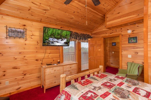 Queen bedroom with wall mounted television at Pool'n Around in the Smokies, a 4 bedroom cabin rental located in Sevierville