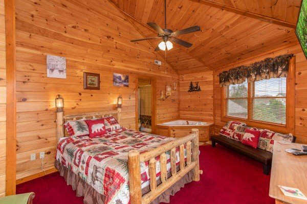 Queen sized log bed next to a jacuzzi at Pool'n Around in the Smokies, a 4 bedroom cabin rental located in Sevierville