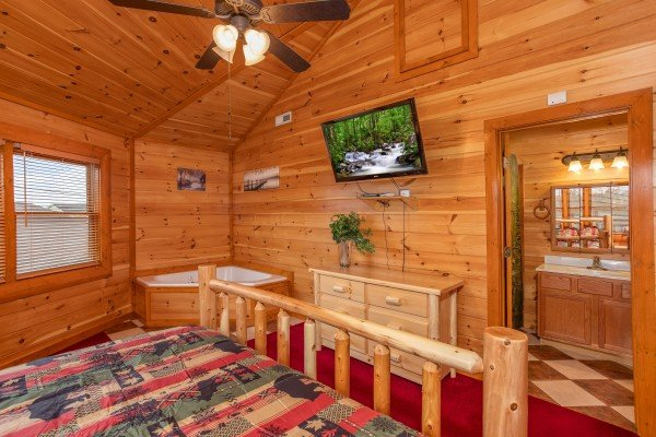 jacuzzi and wall mounted television in king bedroom at amazing sunset serenity a 4 bedroom cabin rental located in sevierville