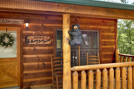 front door under covered porch with a bear hanging on the post at honey bear haven a 1 bedroom cabin rental located in pigeon forge
