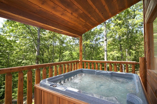 Hot tub under covered deck at Honey Bear Haven, a 1 bedroom cabin rental located in Pigeon Forge