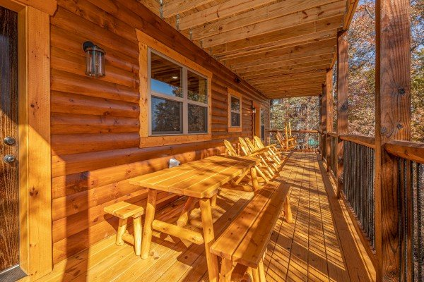 Picnic table and rocking chairs on a covered deck at Pinot Splash, a 4 bedroom cabin rental located in Gatlinburg