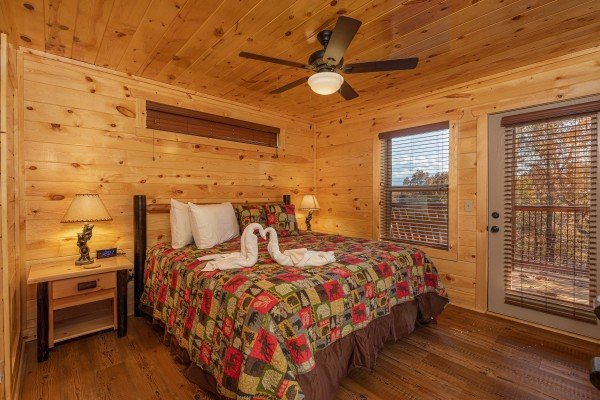 Bedroom with two night stands and lamps and deck access at Pinot Splash, a 4 bedroom cabin rental located in Gatlinburg