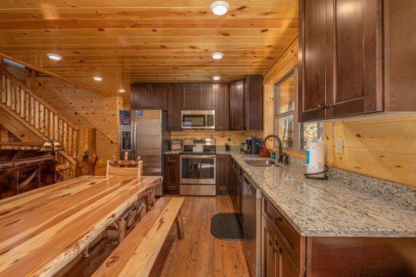 Kitchen with stainless appliances, granite counters, and dining space at Pinot Splash, a 4 bedroom cabin rental located in Gatlinburg