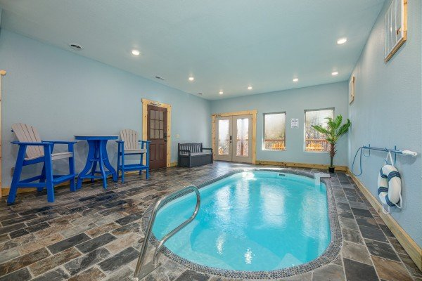 Indoor pool, table with chairs, and bench in the pool area at Pinot Splash, a 4 bedroom cabin rental located in Gatlinburg