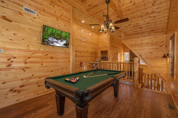 Pool table and TV in the loft at Pinot Splash, a 4 bedroom cabin rental located in Gatlinburg