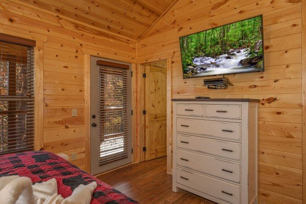 Dresser, TV, and deck access in a bedroom at Pinot Splash, a 4 bedroom cabin rental located in Gatlinburg
