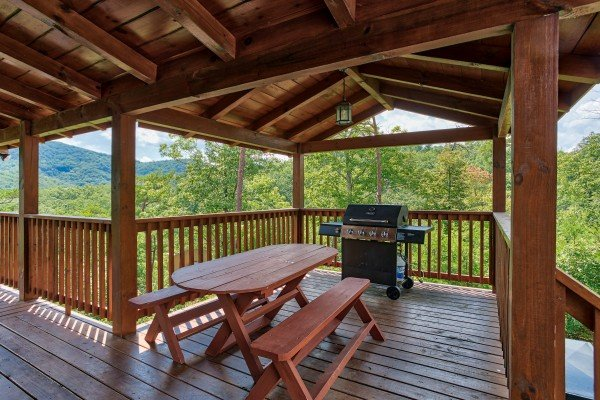 A propane grill and picnic table on the covered deck at Four Seasons Lodge, a 3-bedroom cabin rental located in Pigeon Forge