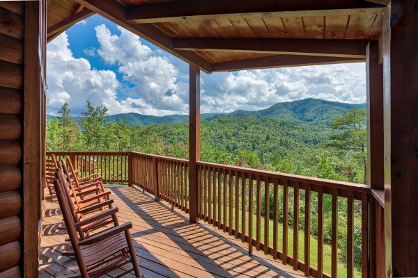 Rocking chairs on the covered deck with mountain views at Four Seasons Lodge, a 3-bedroom cabin rental located in Pigeon Forge