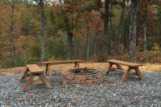Fire pit with bench seats at at Four Seasons Lodge, a 3-bedroom cabin rental located in Pigeon Forge