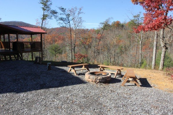 Looking at the fire pit and covered deck in the fall Four Seasons Lodge, a 3-bedroom cabin rental located in Pigeon Forge