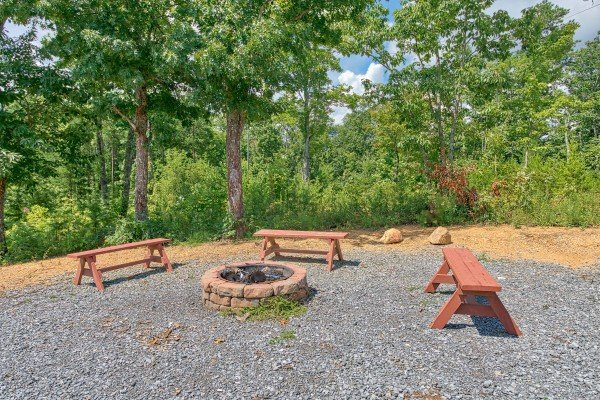 Fire pit with three benches at Four Seasons Lodge, a 3-bedroom cabin rental located in Pigeon Forge