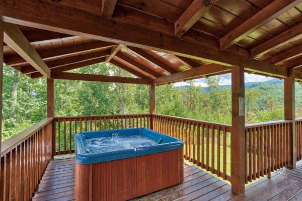 Hot tub on a covered deck at Four Seasons Lodge, a 3-bedroom cabin rental located in Pigeon Forge