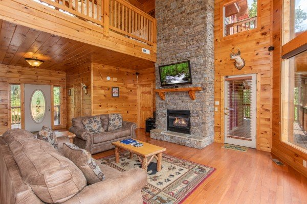 Vaulted living room with tall fireplace and deck access at Four Seasons Lodge, a 3-bedroom cabin rental located in Pigeon Forge
