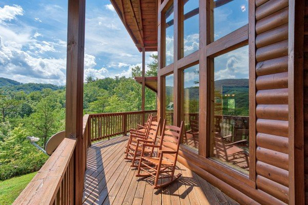Rocking chairs on the covered deck overlooking the mountains at Four Seasons Lodge, a 3-bedroom cabin rental located in Pigeon Forge