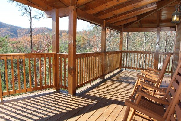 Rocking chairs on a covered deck overlooking the fall colors at Four Seasons Lodge, a 3-bedroom cabin rental located in Pigeon Forge
