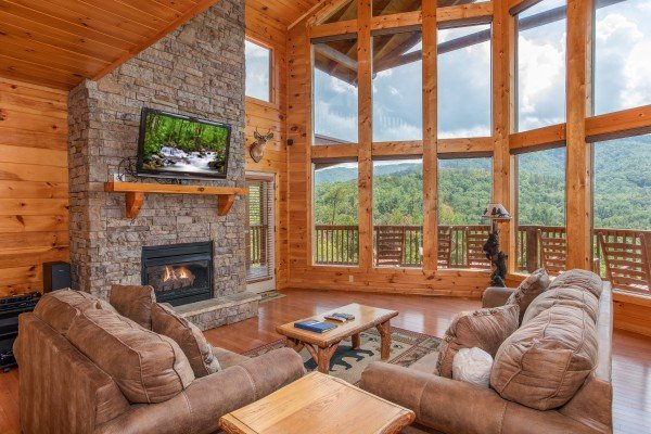 Vaulted ceilings with floor-to-ceiling windows, fireplace, and TV at Four Seasons Lodge, a 3-bedroom cabin rental located in Pigeon Forge