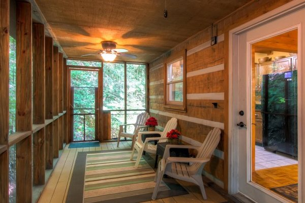 Adirondack chairs on a covered, screened-in porch at Creekside Comfort, a 3-bedroom cabin rental located in Pigeon Forge