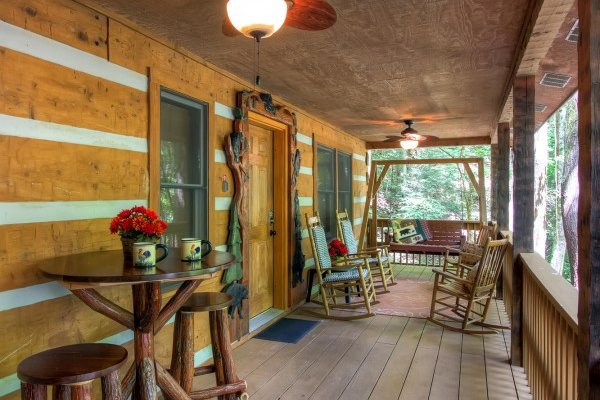 Covered porch with custom woodwork, a swing, and rocking chairs at Creekside Comfort, a 3-bedroom cabin rental located in Pigeon Forge