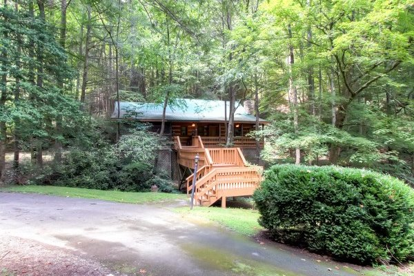 Looking at the cabin and the deck over the creek at Creekside Comfort, a 3-bedroom cabin rental located in Pigeon Forge