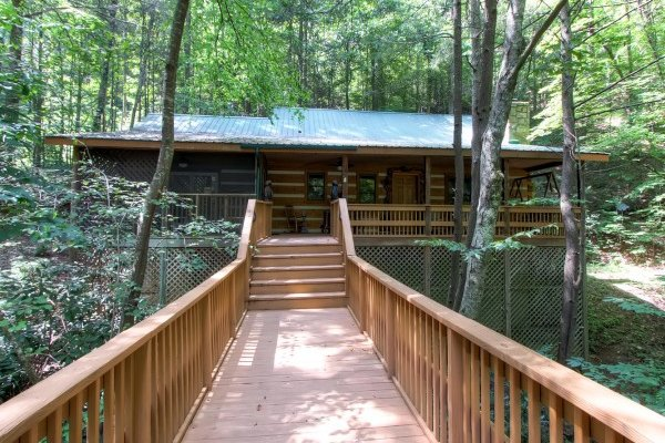 Walkway over the creek to the entrance of Creekside Comfort, a 3-bedroom cabin rental located in Pigeon Forge