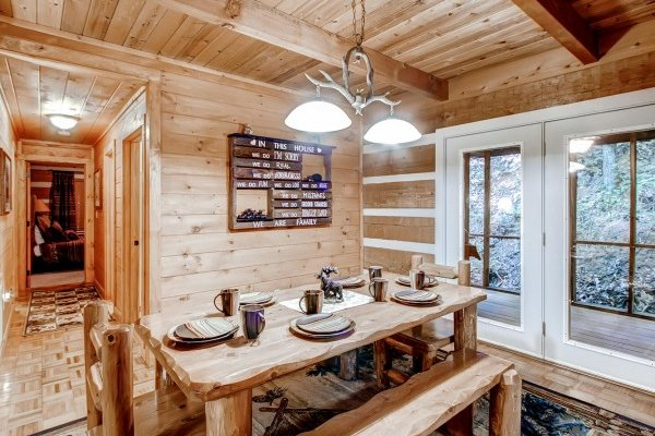 Dining room table with two chairs and two benches with seating for six at Creekside Comfort, a 3-bedroom cabin rental located in Pigeon Forge