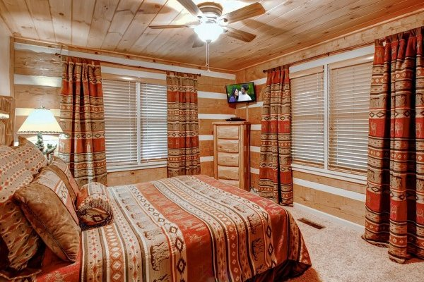 Bedroom with a queen-sized bed, dresser, and television at Creekside Comfort, a 3-bedroom cabin rental located in Pigeon Forge