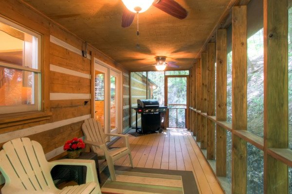 Screened in, covered porch with two Adirondack chairs and a grill at Creekside Comfort, a 3-bedroom cabin rental located in Pigeon Forge