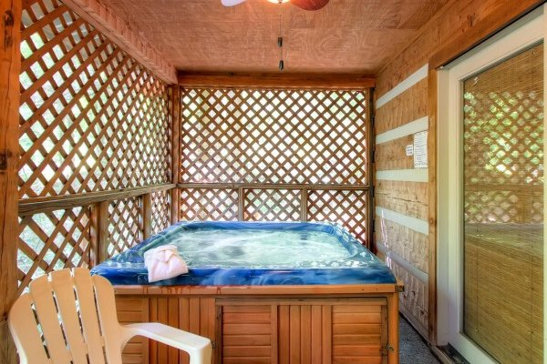 Hot tub with privacy fencing on a covered porch at Creekside Comfort, a 3-bedroom cabin rental located in Pigeon Forge