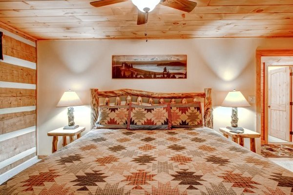 King-sized log bed in a bedroom at Creekside Comfort, a 3-bedroom cabin rental located in Pigeon Forge