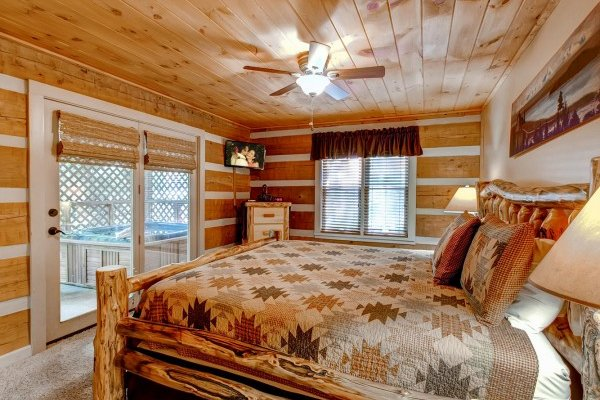 King-sized log bed, dresser, television, and deck access at Creekside Comfort, a 3-bedroom cabin rental located in Pigeon Forge