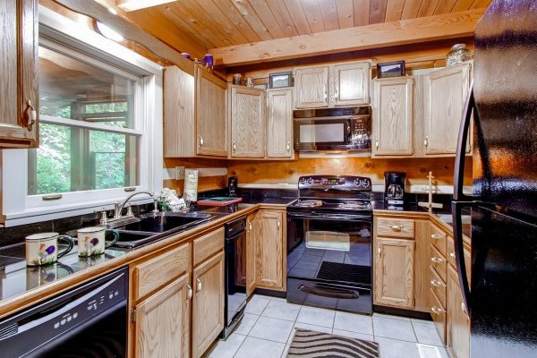 Kitchen with black appliances at Creekside Comfort, a 3-bedroom cabin rental located in Pigeon Forge