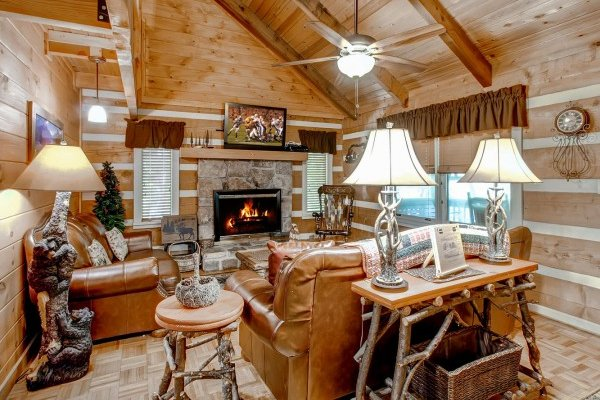 Living room with sofa, loveseat, fireplace, and television at Creekside Comfort, a 3-bedroom cabin rental located in Pigeon Forge