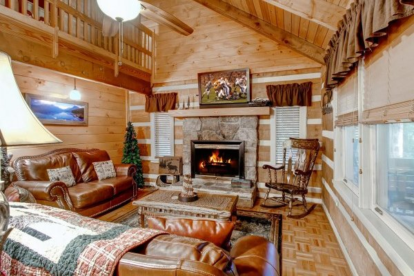Living room with leather sofa, loveseat, fireplace, and tv at Creekside Comfort, a 3-bedroom cabin rental located in Pigeon Forge