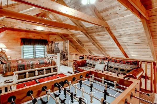 Loft with a bed, sofa, foosball table at Creekside Comfort, a 3-bedroom cabin rental located in Pigeon Forge