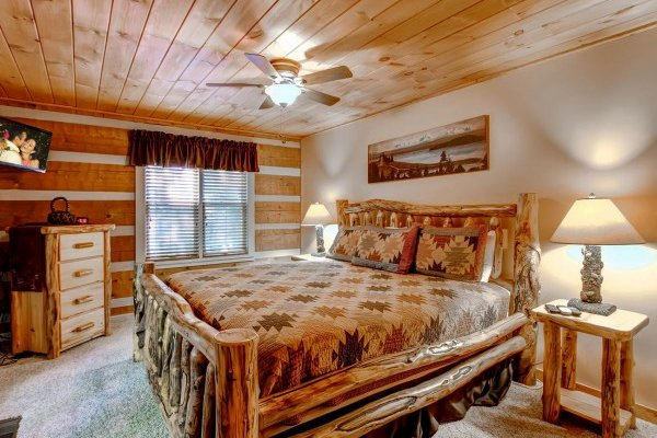 Bedroom with a king-sized bed, dresser, tv, and end tables with lamps at Creekside Comfort, a 3-bedroom cabin rental located in Pigeon Forge