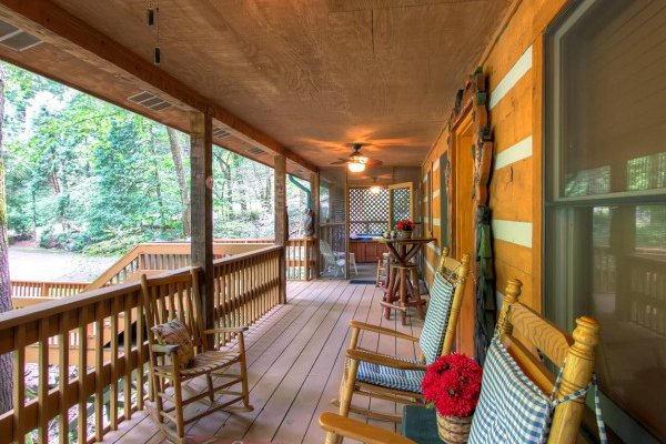 Rocking chairs on the covered deck overlooking the creek at Creekside Comfort, a 3-bedroom cabin rental located in Pigeon Forge