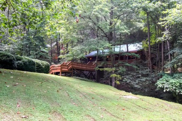 Lawn with views of the creek crossing at Creekside Comfort, a 3-bedroom cabin rental located in Pigeon Forge