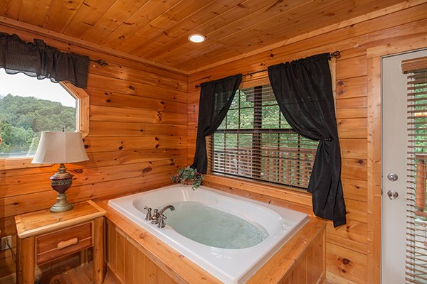 Bedroom jacuzzi near deck access at Family Ties Lodge, a 4-bedroom cabin rental located in Pigeon Forge