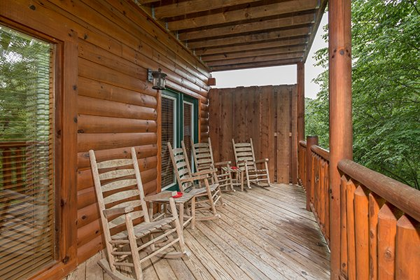Four rocking chairs on a covered deck at Family Ties Lodge, a 4-bedroom cabin rental located in Pigeon Forge