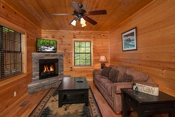 Fireplace and tv in the lower level living room at Family Ties Lodge, a 4-bedroom cabin rental located in Pigeon Forge