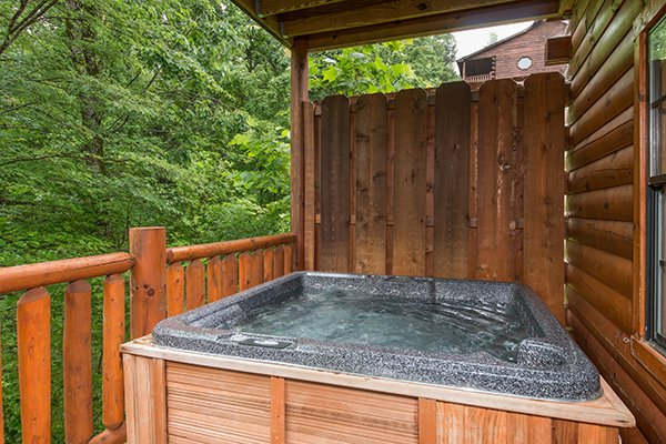 Hot tub with privacy fence at Family Ties Lodge, a 4-bedroom cabin rental located in Pigeon Forge