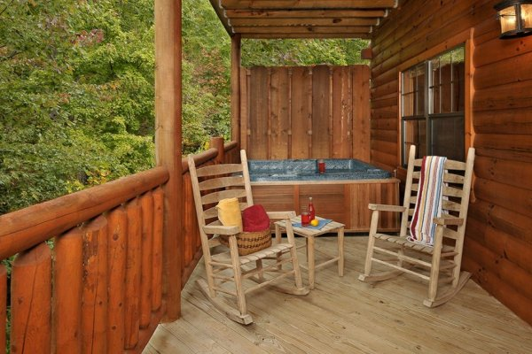 Hot tub with privacy fence and wooded views near two rocking chairs at Family Ties Lodge, a 4-bedroom cabin rental located in Pigeon Forge