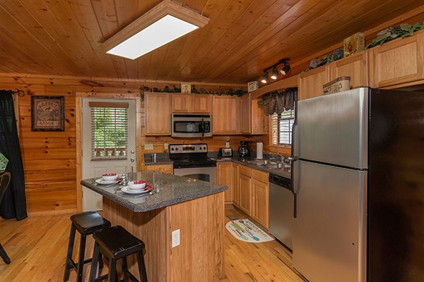 Kitchen with counter top seating and stainless steel appliances at Family Ties Lodge, a 4-bedroom cabin rental located in Pigeon Forge
