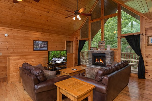 A living room with vaulted ceiling, large windows, fireplace, and  TV at Family Ties Lodge, a 4-bedroom cabin rental located in Pigeon Forge