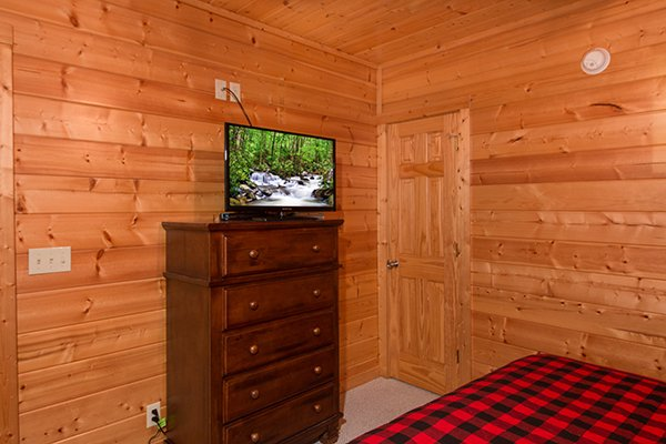 Bedroom with a dresser and television at Family Ties Lodge, a 4-bedroom cabin rental located in Pigeon Forge