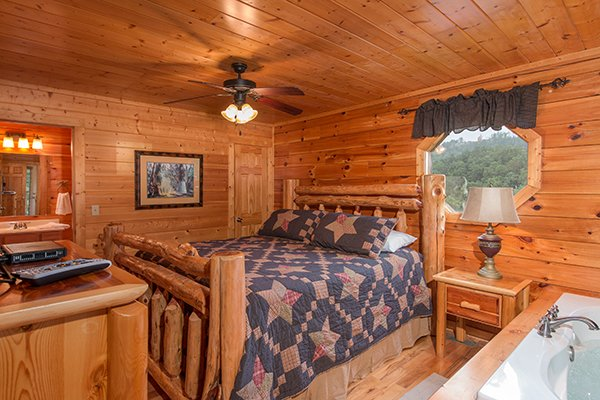 Bedroom with a king bed, jacuzzi, and en suite bath at Family Ties Lodge, a 4-bedroom cabin rental located in Pigeon Forge