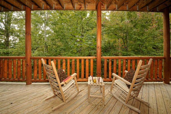 Two rocking chairs overlooking the woods at Family Ties Lodge, a 4-bedroom cabin rental located in Pigeon Forge