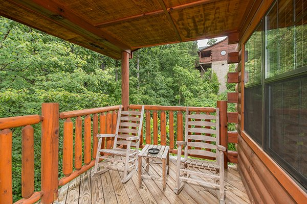 Two rocking chairs on a covered deck at Family Ties Lodge, a 4-bedroom cabin rental located in Pigeon Forge